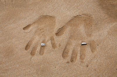 hands and rings in the sand at a Hawaii Wedding