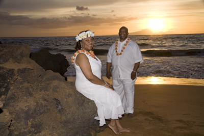 couple taking photos at their sunset hawaii vow renewal