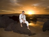groom sits on rocks at his maui wedding