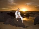 groom sits on rocks at his maui wedding