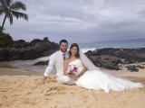 sitting in sand at their Maui Wedding in Hawaii