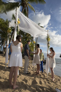 bride's maids hold wedding canopy